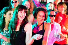 Friends dancing in club or disco. Dance action in a disco club - group of friends, men and women of different ethnicity, dancing to the music having lots of fun Royalty Free Stock Photo