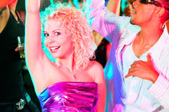 Friends dancing in club or disco. Dance action in a disco club - group of friends, men and women of different ethnicity, dancing to the music having lots of fun Stock Photography