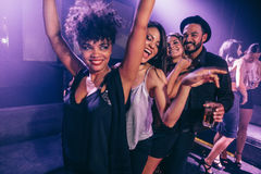 Friends dancing in night club. Group of friends dancing in night club. Young men and women having fun at disco club Stock Photo