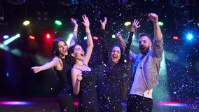 Friends dancing in nightclub with falling confetti. Group of happy young people dancing at a party, on them a multicolored confetti falls. Club spotlights on the stock video footage