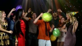 Friends dancing the nightclub fray streamers and. Couple dancing and smiling, together with friends, on colored backgrpund, with bubbles and balloons stock video