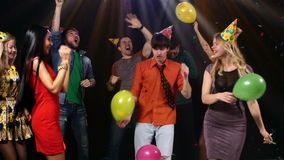 Friends dancing the nightclub fray streamers and. Couple dancing and smiling, together with friends, on colored backgrpund, with bubbles and balloons. Slow stock video footage