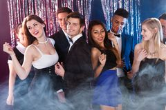 Friends dancing at nightclub. Smiling young friends dancing together at nightclub Royalty Free Stock Photography