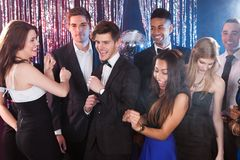 Friends dancing at nightclub. Smiling young friends dancing together at nightclub Royalty Free Stock Images