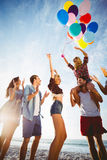 Friends dancing on sand with balloon Stock Image