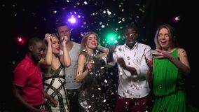 Friends dancing, throwing confetti and makes selfie. Close-up. Slow motion