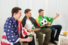 Friends of different nation supporting football team Royalty Free Stock Photo