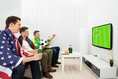 Friends of different nations watching football match Stock Photography
