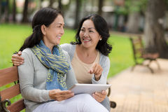 Friends with digital tablet. Female best friends with a digital tablet sitting in the park Stock Images