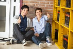 Friends With Digital Tablet Gesturing Thumbsup. Full length portrait of multiethnic friends with digital tablet gesturing thumbsup while sitting in college Royalty Free Stock Image