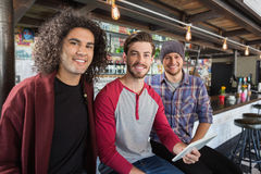 Friends with digital tablet sitting in restaurant. Portrait of male friends with digital tablet sitting in restaurant Royalty Free Stock Image