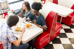 Friends in the diner. Friends eating at the table in the diner Royalty Free Stock Photography
