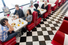 Friends in the diner. Friends eating at the table in the diner stock image