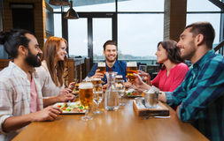 Friends dining and drinking beer at restaurant Royalty Free Stock Photography