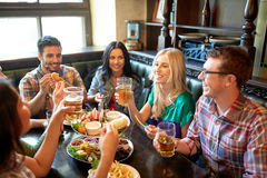 Friends dining and drinking beer at restaurant. Leisure, eating, food and drinks, people and holidays concept - smiling friends having dinner and drinking beer Stock Photos