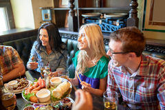 Friends dining and drinking beer at restaurant Royalty Free Stock Image