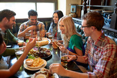 Friends dining and drinking beer at restaurant. Leisure, eating, food and drinks, people and holidays concept - smiling friends having dinner and drinking beer Stock Images