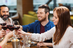 Friends dining and drinking wine at restaurant. Leisure, celebration, food and drinks, people and holidays concept - smiling friends having dinner and drinking Royalty Free Stock Images
