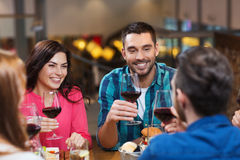 Friends dining and drinking wine at restaurant. Leisure, eating, food and drinks, people and holidays concept - smiling friends having dinner and drinking red Stock Photography