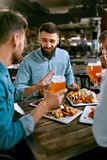 Friends At Dinner Drinking Beer And Eating Food At Restaurant. Friends At Dinner Drinking Beer And Eating Food In Pub Restaurant. High Resolution stock photos