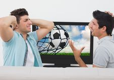 Friends disappointed while watching football match on television Stock Photos