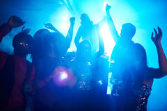 Friends at disco. Friendly guys and girls raising hands while dancing at disco stock photo