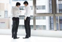 Friends discuss two men during a work break Stock Image