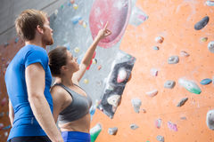 Friends discussing by climbing wall in crossfit gym Stock Images