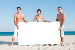 Friends display white placard. Happy smiling group of friends holding a white board for your text at summer beach Royalty Free Stock Image