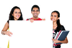 Friends displaying white placard for your text isolated. Group of Indian friends displaying white placard for your text isolated on white background royalty free stock images