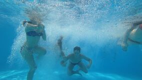 Friends dive in pool young people in swimsuits have fun together jump into the blue pool and swimming underwater. Friends dive into pool young people in stock footage