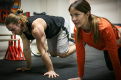 Friends doing exercises in a gym with straps. Royalty Free Stock Images
