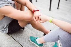 Friends doing gesture of fist bumping. Give me power five. Young men and healthy women fist bumping after a good workout while having a rest on the stairs Royalty Free Stock Photography