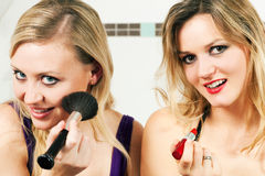 Friends doing make-up. Two female friends applying lipstick and make-up with a brush - presumably to get ready for a party Royalty Free Stock Images