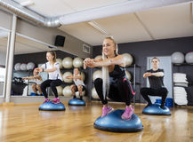 Friends Doing Squatting Exercise On Bosu Ball In Gymnasium Stock Images