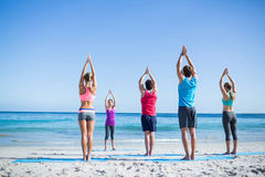Friends doing yoga together with their teacher. At the beach Stock Images