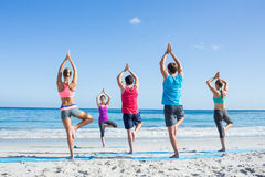 Friends doing yoga together with their teacher. At the beach Royalty Free Stock Photos