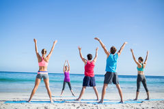 Friends doing yoga together with their teacher. At the beach Stock Image