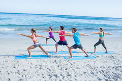 Friends doing yoga together with their teacher. At the beach Royalty Free Stock Photo