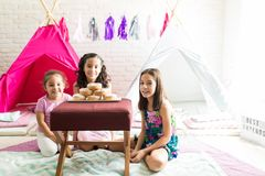 Friends With Donuts Enjoying Sleepover Party At Home. Portrait of cute friends with donuts enjoying sleepover party at home royalty free stock images