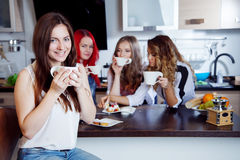 Friends drink tea and coffee at kitchen, portrait of  young beautiful brunette in the foreground, woman with white cup Royalty Free Stock Photos