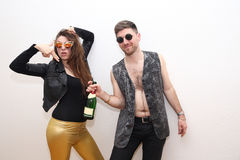 Friends drinking alcohol from the bottle and posing at party Stock Photography