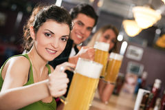 Friends drinking beer in bar. Group of three friends in a bar drinking beer - selective focus on beautiful woman in front zipping from her glass royalty free stock images