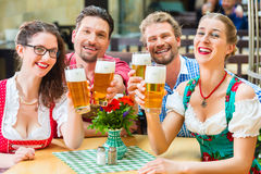 Friends drinking beer in Bavarian restaurant or pub Stock Image