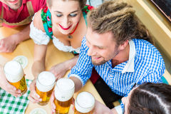 Friends drinking beer in Bavarian restaurant or pub Royalty Free Stock Photography