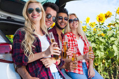 Friends drinking beer bottles sitting in car trunk outdoor countryside Stock Image