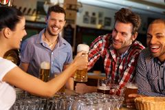 Friends drinking beer at counter in pub. Happy friends drinking beer at counter in pub, chatting with female bartender, smiling Royalty Free Stock Image