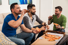 Friends drinking beer and eating pizza Stock Images
