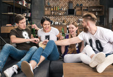 Friends drinking beer and eating popcorn. Cheerful young friends drinking beer and eating popcorn on sofa Stock Images