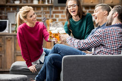Friends drinking beer. Happy young friends drinking beer and clinking glasses Royalty Free Stock Photo
